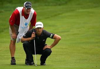 Caddy Joe LaCava and Dustin Johnson study a putt at the 2011 Barclay's