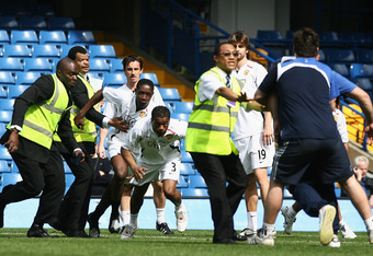 LONDON - APRIL 26:  Patrice Evra of Manchester United (C) and team mates clash with groundstaff following the Barclays Premier League match between Chelsea and Manchester United at Stamford Bridge on April 26, 2008 in London, England.  (Photo by Mike Hewi