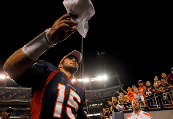 DENVER, CO - AUGUST 20:  Quarterback Tim Tebow #15 of the Denver Broncos throws a towel to a fan as he exits the field after a pre-season game against the Buffalo Bills at Sports Authority Field at Mile High on August 20, 2011 in Denver, Colorado. The Bro
