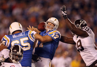 SAN DIEGO, CA - OCTOBER 19: Quarterback Phillip Rivers #17 of the San Diego Chargers losses the ball for a sack as he is pressured by Defensive Linebacker Vonnie Holliday #99 of the Denver Broncos during the second half during Monday Night Football on Oct