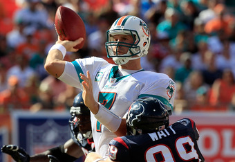 MIAMI GARDENS, FL - SEPTEMBER 18:  Miami Dolphins quarterback Chad Henne #7 attempts a pass whille being pressured by Houston Texans defensive end J.J. Watt #99 during a game at Sun Life Stadium on September 18, 2011 in Miami Gardens, Florida.  (Photo by