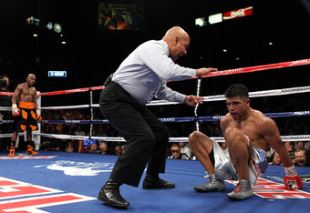 LAS VEGAS, NV - SEPTEMBER 17:  (C) Referee Joe Cortez calls the fight after (L) Victor Ortiz is knocked out by Floyd Mayweather Jr. during their WBC welterweight title fight at the MGM Grand Garden Arena on September 17, 2011 in Las Vegas, Nevada.  (Photo