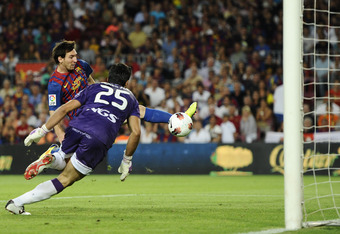 BARCELONA, SPAIN - SEPTEMBER 17: Lionel Messi of FC Barcelona scores his first goal under a challenge by Andres Fernandez Moreno of CA Osasuna during the La Liga soccer match between FC Barcelona and CA Osasuna at Camp Nou Stadium on September 17, 2011 in