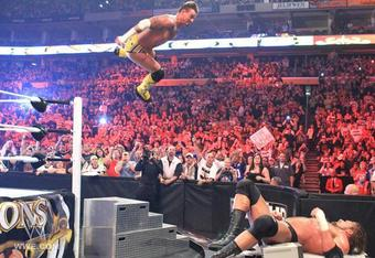 CM Punk flies through the air with a savage elbow drop onto Triple H (Photo by WWE.com)