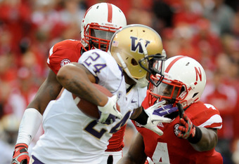LINCOLN, NE - SEPTEMBER 17: Jesse Callier #24 of the Washington Huskies tries to avoid Lavonte David #4 of the Nebraska Cornhuskers during their game at Memorial Stadium September 17, 2011 in Lincoln, Nebraska. Nebraska won 51-38.(Photo by Eric Francis/Ge