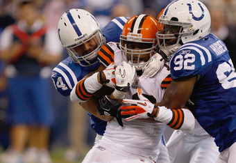 INDIANAPOLIS, IN - SEPTEMBER 18: Jushua Cribbs #16 of the Cleveland Browns is tackled by Jerry Hughes #92 and Drake News #94 of the Indianapolis Colts at Lucas Oil Stadium on September 18, 2011 in Indianapolis, Indiana. The Browns defeated the Colts 27-19