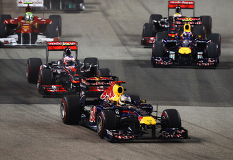 SINGAPORE - SEPTEMBER 25:  Sebastian Vettel of Germany and Red Bull Racing leads into the first corner at the start of the Singapore Formula One Grand Prix at the Marina Bay Street Circuit on September 25, 2011 in Singapore.  (Photo by Vladimir Rys/Getty