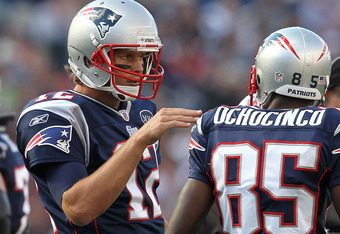 FOXBORO, MA -  SEPTEMBER 18:  Tom Brady #12 of the New England Patriots confers with  Chad Ochocinco #85 of the New England Patriots during a game with the San Diego Chargers at Gillette Stadium on September 18, 2011 in Foxboro, Massachusetts. (Photo by J