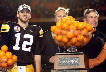 MIAMI GARDENS, FL - JANUARY 05:  Ricky Stanzi #12 and head coach Kirk Ferentz  (R) of the Iowa Hawkeyes celebrate with the throphy after Iowa won 24-14 against the Georgia Tech Yellow Jackets during the FedEx Orange Bowl at Land Shark Stadium on January 5