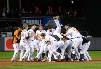 BALTIMORE, MD - SEPTEMBER 28:  Robert Andino #11 of the Baltimore Orioles is mobbed by teammates after driving in the game winning run in the ninth inning against the Boston Red Sox at Oriole Park at Camden Yards on September 28, 2011 in Baltimore, Maryla