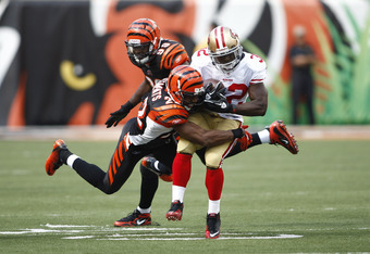 CINCINNATI, OH - SEPTEMBER 25:  Kendall Hunter #32 of the San Francisco 49ers is tackled by Nate Clements #22 of the Cincinnati Bengals during their game on September 25, 2011 at Paul Brown Stadium in Cincinnati, Ohio.  The 49ers defeated the Bengals 13-8