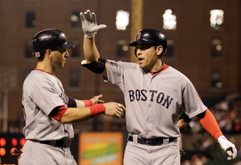 BALTIMORE, MD - SEPTEMBER 27:  Jacoby Ellsbury #2 of the Boston Red Sox (R) celebrates after driving in Marco Scutaro #10 (L) on a home run against the Baltimore Orioles during the third inning at Oriole Park at Camden Yards on September 27, 2011 in Balti