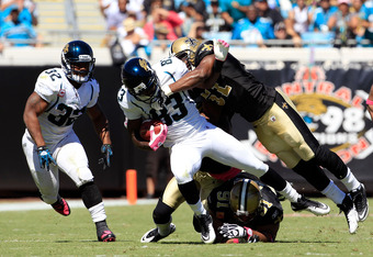 JACKSONVILLE, FL - OCTOBER 02:   Jason Hill #83 of the Jacksonville Jaguars is tackled by  Jonathan Vilma #51 of the New Orleans Saints during a game at EverBank Field on October 2, 2011 in Jacksonville, Florida.  (Photo by Sam Greenwood/Getty Images)
