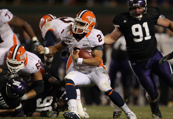 CHICAGO - NOVEMBER 20: Nathan Scheelhaase #2 of the Illinois Fighting Illini runs pursued by Brian Arnfelt #91 of the Northwestern Wilcats during a game played at Wrigley Field on November 20, 2010 in Chicago, Illinois. Illinois defeated Northwestern 48-2