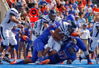 BOISE, ID - OCTOBER 01:  Tyler Lantrip #16 of the Nevada Wolf Pack is brought down by Tyrone Crawford #40 and Billy Winn #90 of the Boise State Broncos at Bronco Stadium on October 1, 2011 in Boise, Idaho.  (Photo by Otto Kitsinger III/Getty Images)