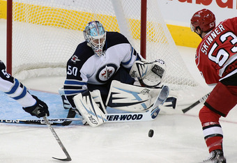 WINNIPEG, CANADA - SEPTEMBER 28: Chris Mason #50 of the Winnipeg Jets blocks a shot on net by Jeff Skinner #53 of the Carolina Hurricanes in preseason NHL action at the MTS Centre on September 28, 2011 in Winnipeg, Manitoba, Canada. (Photo by Marianne Hel