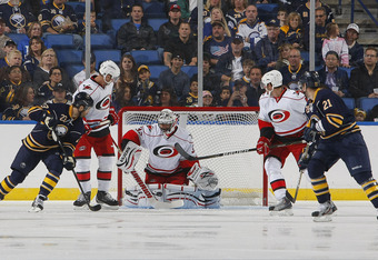 BUFFALO NY - SEPTEMBER 19:  Ville Leino #23 of the Buffalo Sabres along with teammate Drew Stafford #21 look along side of Tim Brent #37 and Jamie McBain #4 of the Carolina Hurricanes as Brian Boucher #33 of the Carolina Hurricanes makes a save during the