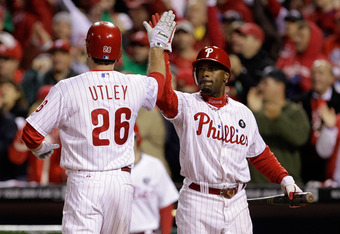 PHILADELPHIA, PA - OCTOBER 02:  Jimmy Rollins #11 and Chase Utley #26 of the Philadelphia Phillies celebrate after scoring on a Ryan Howard #6 RBI single in the first inning against the St. Louis Cardinals in Game Two of the National League Division Serie