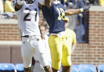 ANN ARBOR - SEPTEMBER 18:  Wide receiver Jermaine Gonzales #18 of the San Diego State University Aztecs and defensive back Marcus Demps #21 of the University of Michigan Wolverines attempt to make a catch during the game at Michigan Stadium on September 1