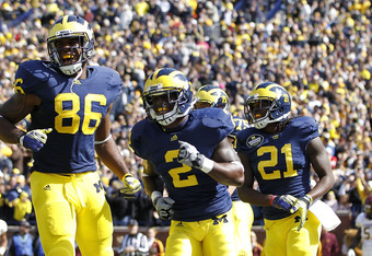 ANN ARBOR, MI - OCTOBER 01: Vincent Smith #2 of the Michigan Wolverines scores on a 28-yard pass from teammate Denard Robinson #16 and celebrates with teammates Kevin Koger #86 and Junior Hemingway #21 during the second quarter of the game against the Min