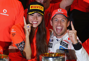 SUZUKA, JAPAN - OCTOBER 09:  Jenson Button of Great Britain and McLaren celebrates in the pitlane with his girlfriend Jessica Michibata and team mates after winning the Japanese Formula One Grand Prix at Suzuka Circuit on October 9, 2011 in Suzuka, Japan.