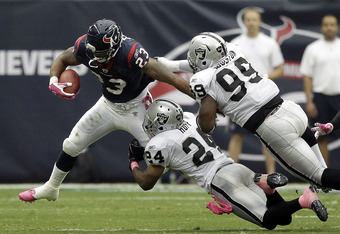 HOUSTON - OCTOBER 09:  Running back Arian Foster #23 of the Houston Texans looks for room to run as he is tackled by saftey Michael Huff #24 and defensive end Lamarr Houston #99 at Reliant Stadium on October 9, 2011 in Houston, Texas.  (Photo by Bob Levey