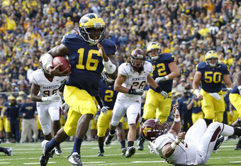 ANN ARBOR, MI - OCTOBER 01:  Denard Robinson #16 of the Michigan Wolverines runs 9 yards for a first quarter touchdown during the game against the Minnesota Golden Gophers at Michigan Stadium on October 1, 2011 in Ann Arbor, Michigan.  (Photo by Leon Hali