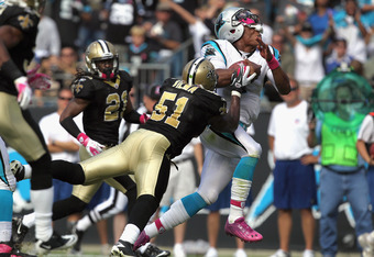 Cam Newton has his helmet nearly knocked off on this hard hit by Jonathan Vilma, but not before gaining 13 yards on an option-quarterback keeper in the fourth quarter.