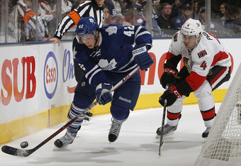 TORONTO, CANADA - OCTOBER 8: Tyler Bozak #42 of the Toronto Maple Leafs gets around Chris Phillips #4 of the Ottawa Senators during NHL action at the Air Canada Centre October 8, 2011 in Toronto, Ontario, Canada. (Photo by Abelimages/Getty Images)