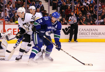 VANCOUVER, CANADA - OCTOBER 6:  Mark Letestu #10 of the Pittsburgh Penguins is checked by Daniel Sedin #22  of the Vancouver Canucks during the second period at Rogers ArenaOctober 6, 2011 in Vancouver, British Columbia, Canada. (Photo by Marissa Baecker/