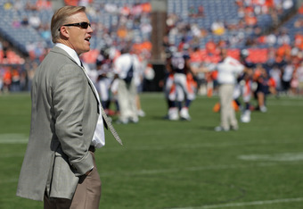 DENVER, CO - SEPTEMBER 18:  John Elway, Executive Vice President of Football Operations for the Denver Broncos, looks on from the bench as the Broncos warm up prior to facing the Cincinnati Bengals at Invesco Field at Mile High on September 18, 2011 in De