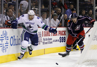 COLUMBUS, OH - OCTOBER 10:  Maxim Lapierre #40 of the Vancouver Canucks and David Savard #58 of the Columbus Blue Jackets battle for a puck during the game at Nationwide Arena on October 10, 2011 in Columbus, Ohio.  The Canucks defeated the Blue Jackets 3