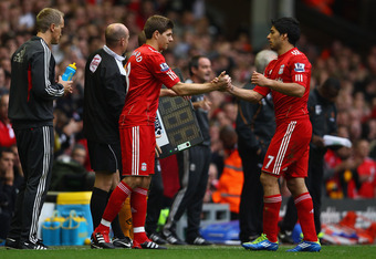 LIVERPOOL, ENGLAND - SEPTEMBER 24:  Steven Gerrard (C) of Liverpool shakes hands with team mate Luis Suarez before coming on as a substitute during the Barclays Premier League match between Liverpool and Wolverhampton Wanderers at Anfield on September 24,