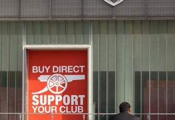 LONDON, ENGLAND - APRIL 11:  A man sits in front of the fan shop of Arsenal Football Club's Emirates Stadium on April 11, 2011 in London, England. American businessman Stan Kroenke's company 'Kroenke Sports Enterprises' has increased its shareholding in A