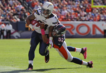 DENVER, CO - OCTOBER 09:  Running back Ryan Mathews #24 of the San Diego Chargers runs with the ball as linebacker Wesley Woodyard #52 of the Denver Broncos makes the tackle at Sports Authority Field at Mile High on October 9, 2011 in Denver, Colorado. Th