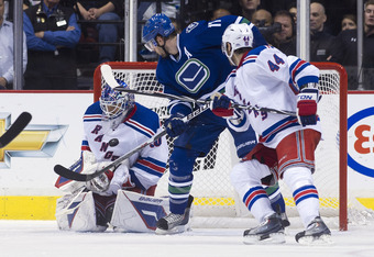 VANCOUVER, CANADA - OCTOBER 18: Goalie Henrik Lundqvist #30 of the New York Rangers makes a save while Ryan Kesler #17 of the of the Vancouver Canucks and Steve Eminger #44 of the New York Rangers look on during the second period in NHL action on October