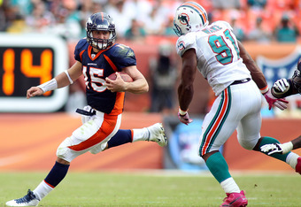 MIAMI GARDENS, FL - OCTOBER 23:  Quarterback Tim Tebow #15 of the Denver Broncos rolls out against Cameron Wake #91 of the Miami Dolphins to end the game to overtime at Sun Life Stadium on October 23, 2011 in Miami Gardens, Florida. Denver defeated Miami