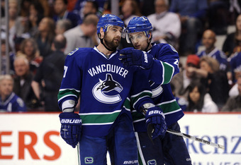 VANCOUVER, CANADA - MAY 18:  Christopher Higgins #20 and Mason Raymond #21 of the Vancouver Canucks confer during a break in Game Two of the Western Conference Finals against San Jose Sharks during the 2011 Stanley Cup Playoffs at Rogers Arena on May 18,