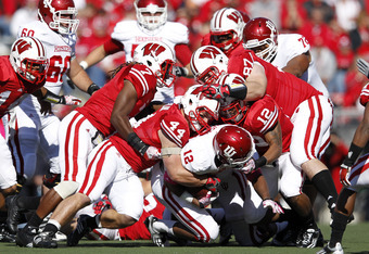 MADISON, WI - OCTOBER 15: A group of Wisconsin Badgers defenders make a tackle against Stephen Houston #12 of the Indiana Hoosiers at Camp Randall Stadium on October 15, 2011 in Madison, Wisconsin. The Badgers won 59-7. (Photo by Joe Robbins/Getty Images)