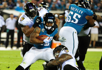 JACKSONVILLE, FL - OCTOBER 24:  Ray Lewis #52 and Terrell Suggs #55 of the Baltimore Ravens tackle Maurice Jones-Drew #32 of the Jacksonville Jaguars at EverBank Field on October 24, 2011 in Jacksonville Florida. (Photo by Scott Cunningham/Getty Images)