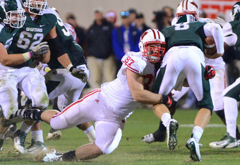 EAST LANSING, MI - OCTOBER 22:  Ethan Hemer #87 of the Wisconsin Badgers sacks Kirk Cousins #8 of the Michigan State Spartans in the fourth quarter of the game at Spartan Stadium on October 22, 2011 in East Lansing, Michigan. The Spartans defeated the Bad