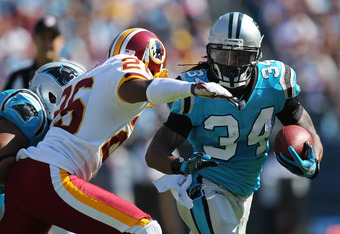 CHARLOTTE, NC - OCTOBER 23:  DeAngelo Williams #34 of the Carolina Panthers runs past the tackle of Josh Wilson #26 of the Washington Redskins during their game at Bank of America Stadium on October 23, 2011 in Charlotte, North Carolina.  (Photo by Scott