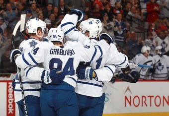 OTTAWA, CANADA - OCTOBER 30: Mikhail Grabovski #84 of the Toronto Maple Leafs celebrates a first period goal with team mates Jake Gardiner #51 and Nikolai Kulemin #41 during an NHL game against the Ottawa Senators at Scotiabank Place on October 30, 2011 i