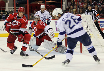 RALEIGH, NC - OCTOBER 07: Bryan Allen #5 and Cam Ward #30 of the Carolina Hurricanes defend the net against Martin St. Louis #26 of the Tampa Bay Lightning at the RBC Center on October 7, 2011 in Raleigh, North Carolina.  (Photo by Bruce Bennett/Getty Ima
