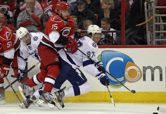 RALEIGH, NC - OCTOBER 07: Tuomo Ruutu #15 of the Carolina Hurricanes hits Matt Gilroy #97 of the Tampa Bay Lightning at the RBC Center on October 7, 2011 in Raleigh, North Carolina. Tampa Bay defeated the Hurricanes 5-1. (Photo by Bruce Bennett/Getty Imag