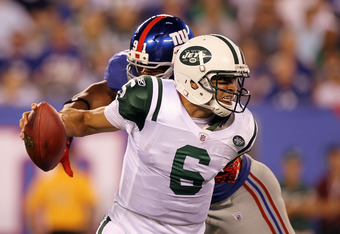 EAST RUTHERFORD, NJ - AUGUST 29:   Mark Sanchez #6 of the New York Jets eludes a sack attempt from Justin Tuck #91 of the New York Giants during their pre season game on August 29, 2011 at MetLife Stadium in East Rutherford, New Jersey.  (Photo by Jim McI