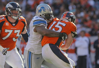 DENVER, CO - OCTOBER 30:  Defensive lineman Corey Williams #99 of the Detroit Lions wraps up quarterback Tim Tebow #15 of the Denver Broncos at Sports Authority at Invesco Field at Mile High on October 30, 2011 in Denver, Colorado. The Lions defeated the