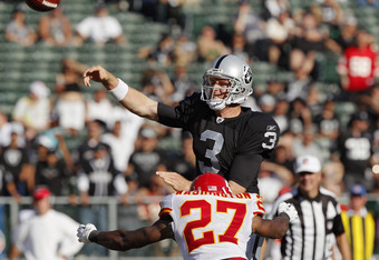 OAKLAND, CA - OCTOBER 23: Quarterback Carson Palmer #3 gets rid of the ball as he gets hit by safety Donald Washington #27 of the Oakland Raiders of the Kansas City Chiefs on October 23, 2011 at O.co Coliseum in Oakland, California. The Chiefs won 28-0. (