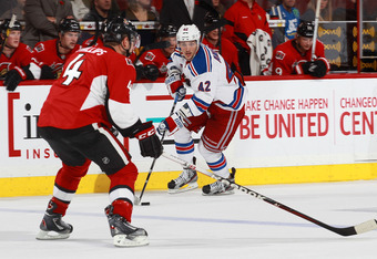 OTTAWA, CANADA - NOVEMBER 9: Artem Anisimov #42 of the New York Rangers skates with the puck against Chris Phillips #4 of the Ottawa Senators during an NHL game at Scotiabank Place on November 9, 2011 in Ottawa, Ontario, Canada.  (Photo by Jana Chytilova/