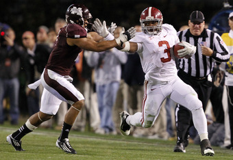 STARKVILLE, MS - NOVEMBER 12:  Running back Trent Richardson #3 of the Alabama Crimson Tide stiff arms defensive back Wade Bonner #7 of the Mississippi State Bulldogs during a big first down run in the fourth quarter on November 12, 2011 at Davis Wade Sta